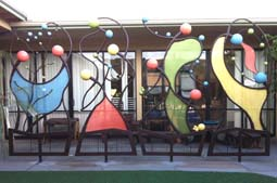 Preschool Screens - These twirling all-steel screens were installed in the courtyard of a Santa Monica (CA) preschool to playfully break up the view into the windows of an adjacent auditorium.  The abstract figures generally reference nurturing/growing, building/cooperation, group playing, and sharing/dancing.  They were unveiled to a wildly enthusiastic mob of tykes. 8ft high x 4ft wide each